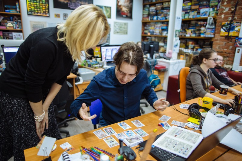 Петр Тюленев, руководитель студии разработки игр Hobby World, разбирает правила новой настольной игры, которую ему прислал автор. Фото: Макс Новиков.